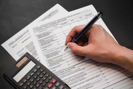 taxation: Man fills out polish tax form Stock Photo