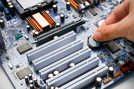 pc repair: Hand install battery to PC motherboard Stock Photo