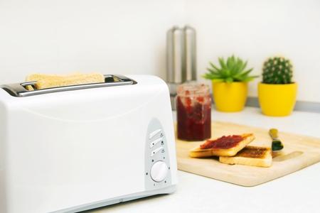 Ontbijt te bereiden. Broodrooster en toast met jam in de moderne keuken Stockfoto