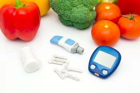 diabetes: Glucosa dispositivo medidor con accesorios. Verduras y estilo de vida saludable