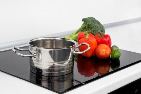 Pot en groenten in de moderne keuken met een inductiekookplaat