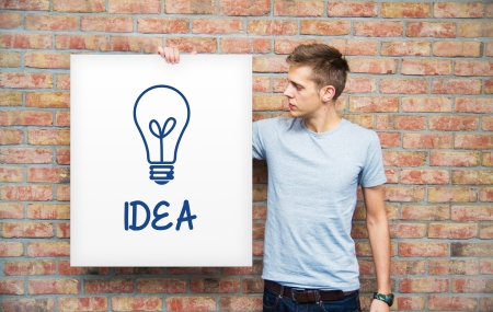 Young man holding whiteboard with idea bulb photo