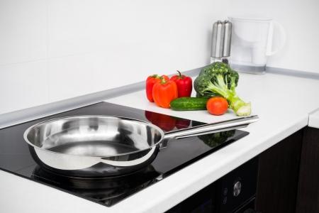Sartén y verduras en la moderna con estufa de inducción Foto de archivo