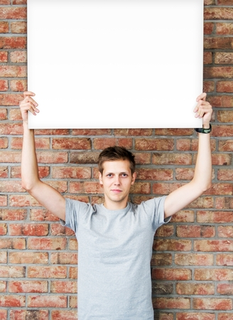 publicity: Young man holding blank whiteboard on business presentation