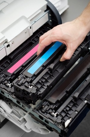 Man puts toner in the printer Фото со стока