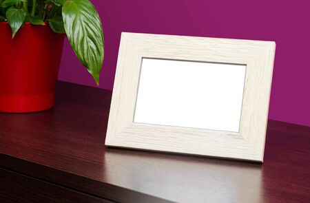 Blank wooden photo frame on the dresser photo