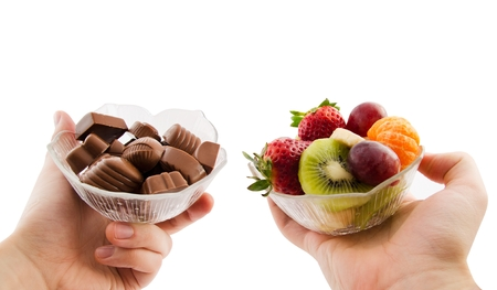 Choose healthy foods. Bowl with chocolates and a bowl of fruit photo