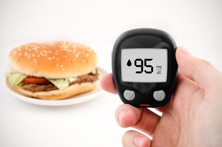 Hand holding meter. Diabetes doing glucose level test. Hamburger photo