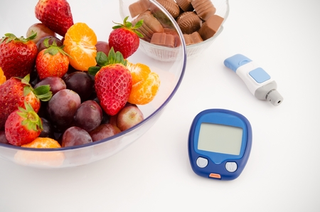 Glucose meter device with accessories. Fruits and chocolates. Healthy lifestyle Zdjęcie Seryjne