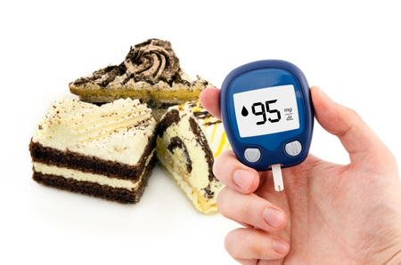 blood sugar: Hand holding meter. Diabetes doing glucose level test. Cake in background