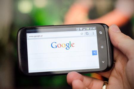 google: Smartphone con el sitio web de b�squeda de Google Editorial