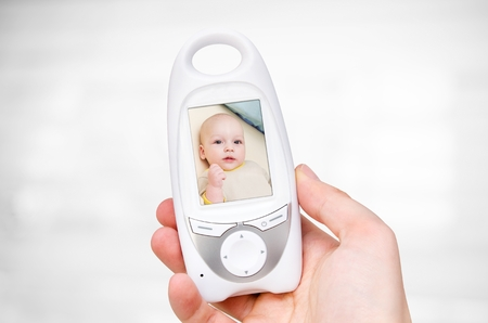 Hand holding video baby monitor for security of the baby  Stock Photo