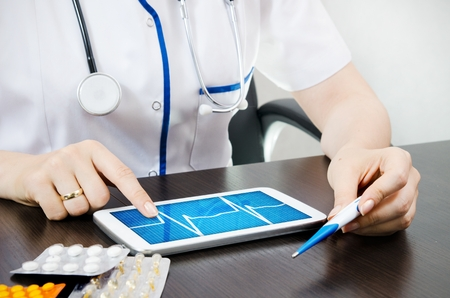 Doctor reads the chart on digital tablet photo