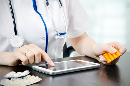 Doctor working on a digital tablet photo