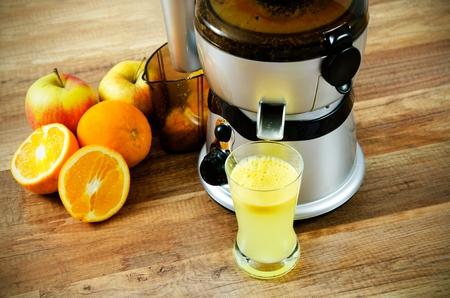 木製の背景にジューサーとオレンジ ジュース