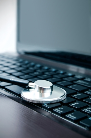 Diagnosis and repair of computers. Stethoscope on laptop photo
