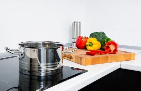pot light: Pot and vegetables in modern kitchen with induction stove