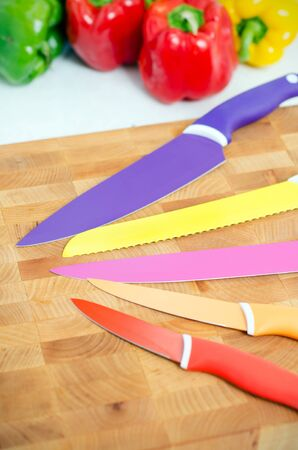 knifes: Ceramic knifes on a chopping board. Fresh vegetables in background