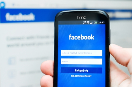 Hand holding smartphone with Facebook social network mobile app with Facebook website in background