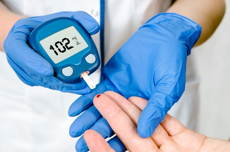 diabetes: Doctor woman measuring glucose level blood in hospital close-up
