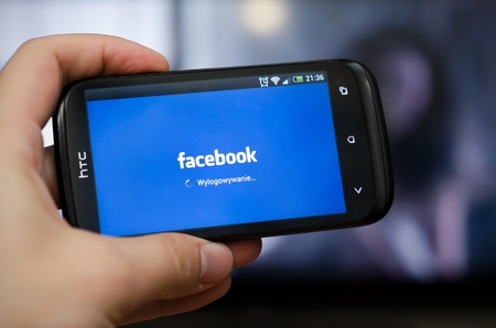 Hand holding smartphone with Facebook social network mobile app