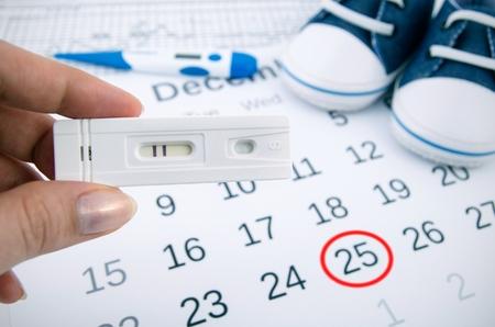 prueba de embarazo: Prueba de embarazo positiva en el calendario con la fecha de nacimiento
