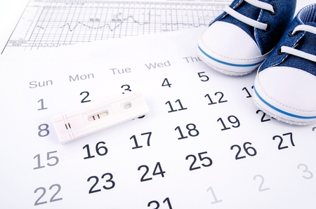 Positive pregnancy test on calendar and baby shoes