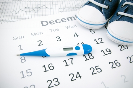 progesterone: Electronic thermometer in fertility concept on calendar