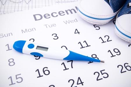 relaciones sexuales: Termómetro electrónico en concepto de la fertilidad en el calendario