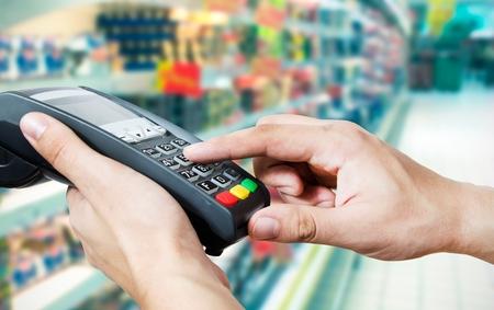 persona leyendo: Mano con golpe de tarjeta de cr�dito a trav�s de terminales de venta en supermercado Foto de archivo