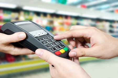 card reader: Hand with credit card swipe through terminal for sale in supermarket Stock Photo