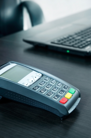 Payment terminal in the office. Laptop in the background photo