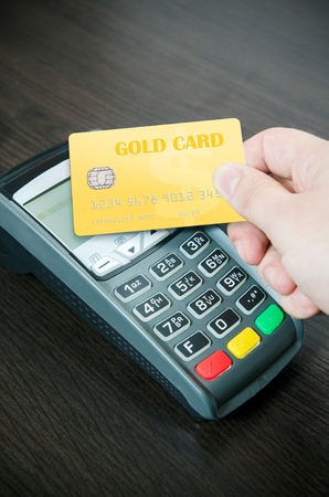 pays: Man pays a gold card in payment terminal
