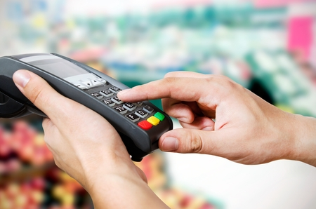 Hand with credit card swipe through terminal for sale in supermarket Stock Photo