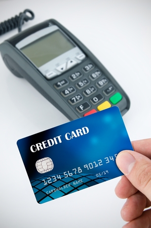 trade credit: Hand holding credit card. Payment terminal in background Stock Photo