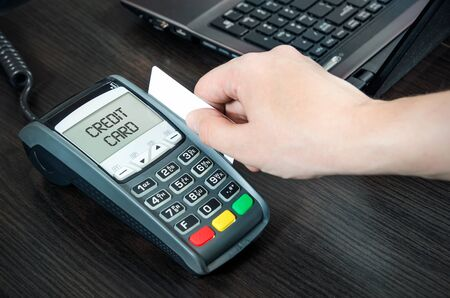 pays: Man pays with credit card. Swiping plastic card through terminal Stock Photo