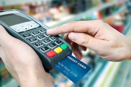 Hand with credit card swipe through terminal for sale in supermarket 스톡 콘텐츠