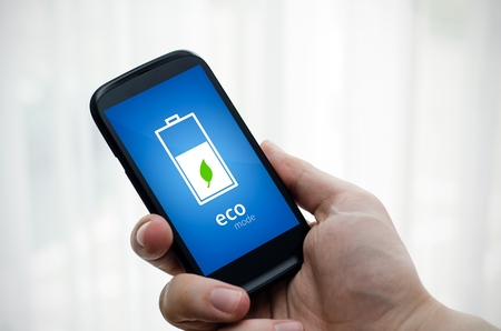 charge: Man holding phone with economic battery mode on display