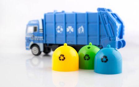 camion de basura: Contenedores de basura de colores y juguetes de camiones de basura en el fondo blanco