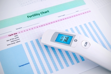 sexual intercourse: Contactless digital thermometer on fertility chart background Stock Photo