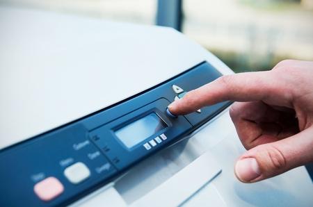 impresora: Hombre que sostiene el dedo en el botón de inicio de la impresora láser Foto de archivo