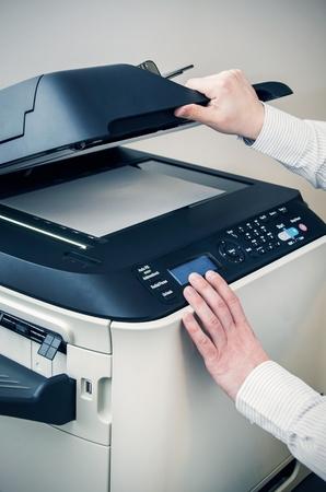 fotocopiadora: Hombre que usa el dispositivo multifunción escáner en la oficina