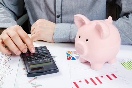 budget crisis: Man calculates money. Piggy bank and business documents on desk Stock Photo