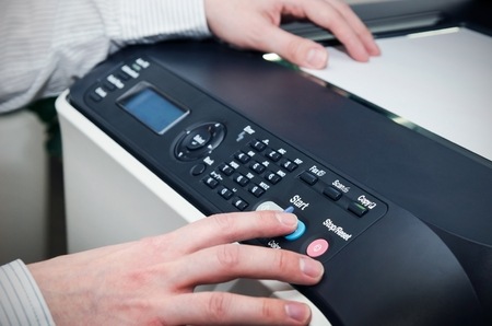 Man using scanner multifunction device in office