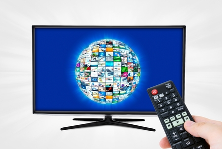 remote communication: Widescreen high definition TV screen with sphere video gallery. Remote control in hand