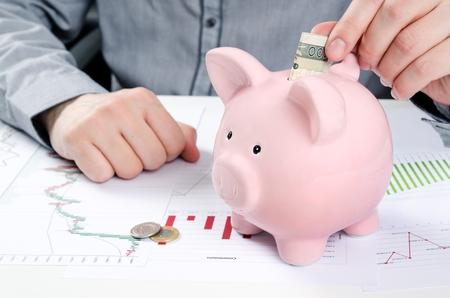 Man putting polish bill in piggy bank. Saving money concept Zdjęcie Seryjne