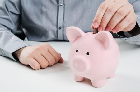 caja fuerte: Hombre que pone la moneda en la hucha. Concepto de ahorro de dinero Foto de archivo