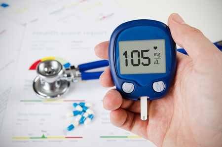 diabetes meter kit: Hand holding glucometer. Stethoscope and pills in background