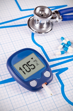diabetes meter kit: Glucometer and stethoscope on medical background Stock Photo