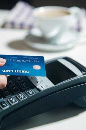 Woman hand using payment terminal in restaurant Standard-Bild